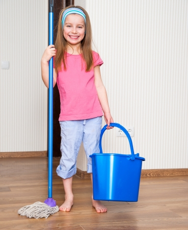 happy little girl washing the floor with a mop photo