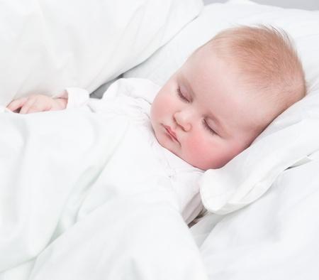 kleines Baby schläft in einem schneeweißen Bett Lizenzfreie Bilder