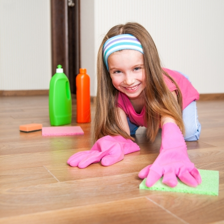 little girl washing the floor with a cloth photo
