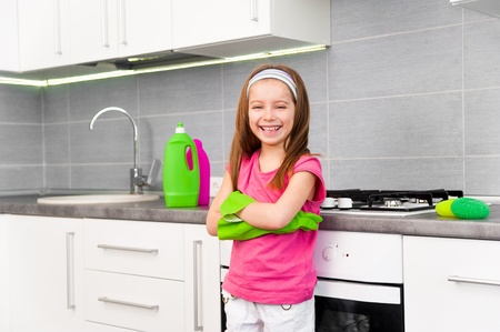 smiling little girl cleans in the kitchen at home photo