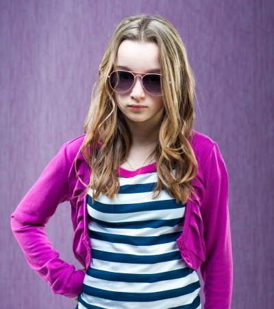 11: portrait of a beautiful little fashion model in sunglasses on a purple background Stock Photo