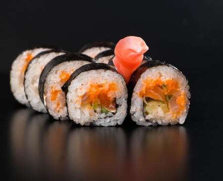 salmon ahumado: Maki sushi sobre fondo negro Foto de archivo
