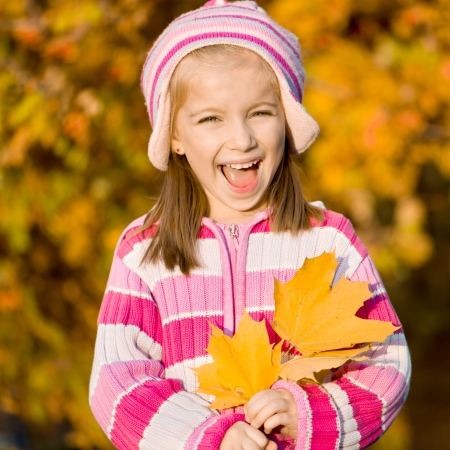 mountain ash: smiling little girl against the leaves of mountain ash