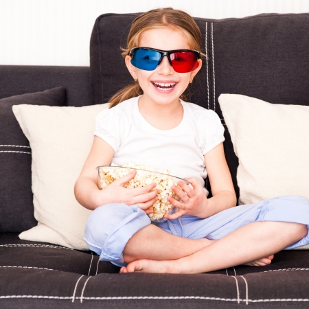 little girl with popcorn watching 3d TV photo