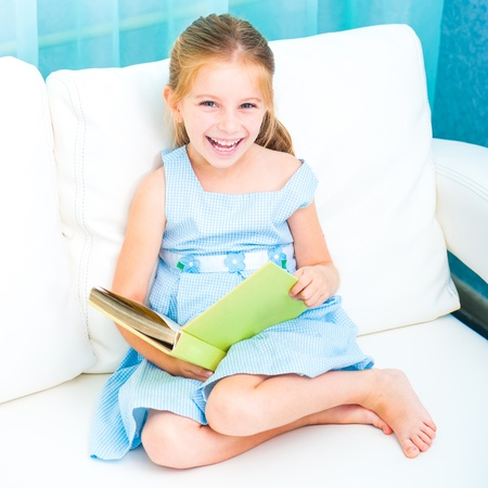 happy little girl reading a book and siting on the sofa