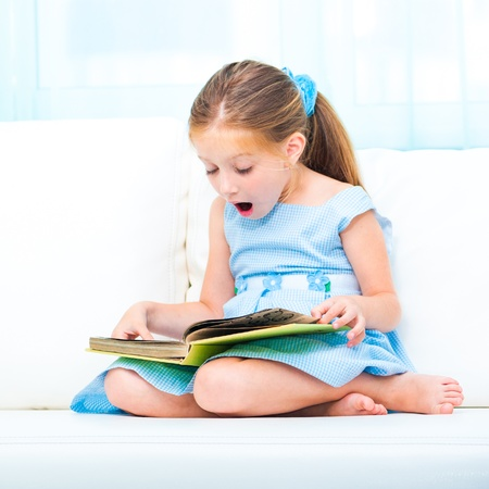 preschoolers: little cute girl reading a book and siting on the sofa Stock Photo