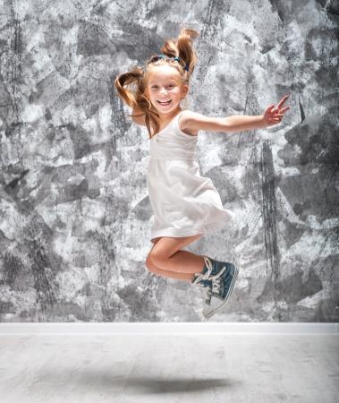 Happy little girl in white dress jump  Studio shot  photo