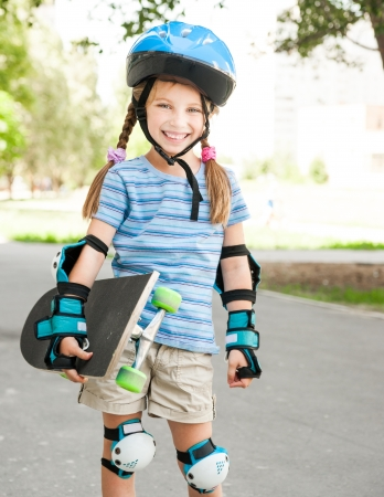 cute little girl in a helmet holding a skate