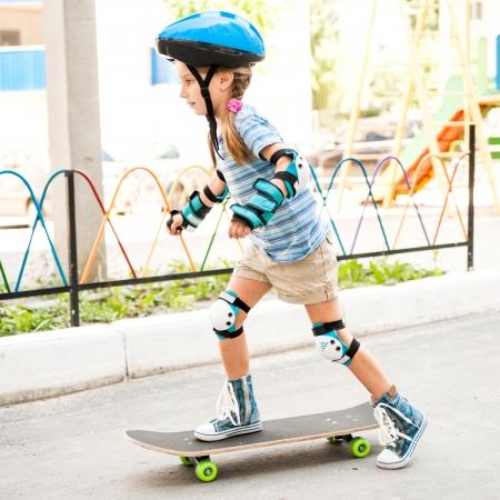 kleines Mädchen mit einem Helm Reiten auf Skateboard im Park