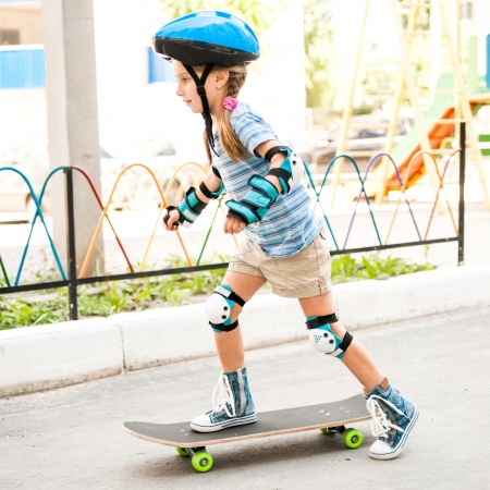 little girl with a helmet riding on skateboard in the park