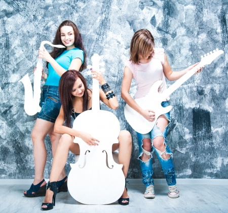 female rock band  girls with musical instruments  guitar, sax and cello photo