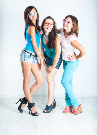 three pretty girls friends in a summer clothes and sunglasses photo