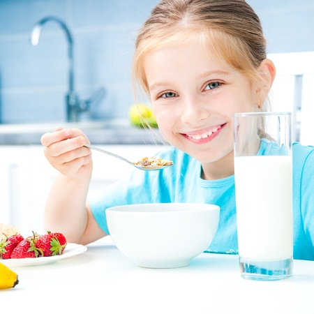 cute little girl eating cereal and strawberries in the white kitchen photo