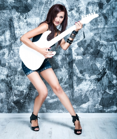 Beautiful rock singer with a white guitar in the studio photo