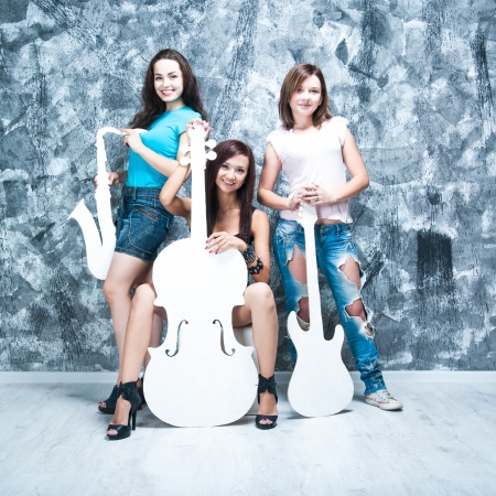 three people only: female rock band  girls with musical instruments  guitar, saxophone and cello