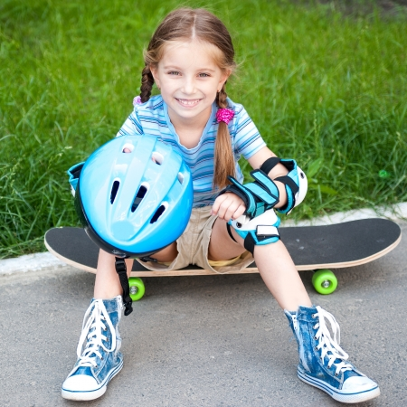 blue helmet: little cute girl sitting on a skateboard in the park