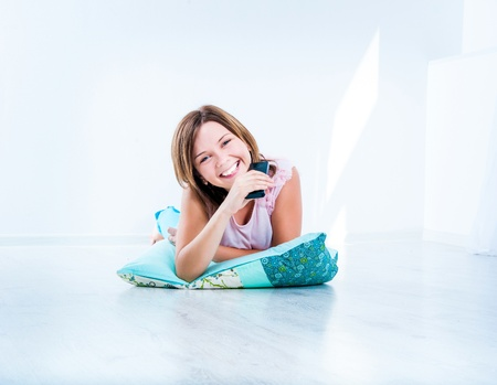 programm: cute girl watching TV lying on the floor Stock Photo