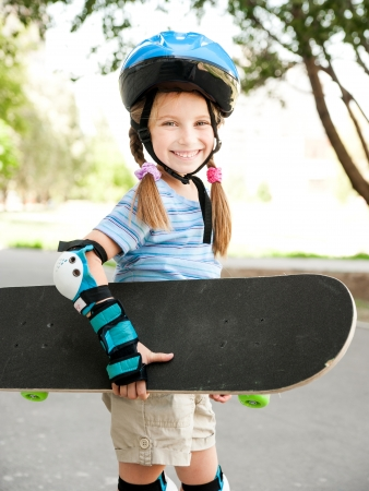 cute little girl in a helmet holding a skate in a park Stock Photo