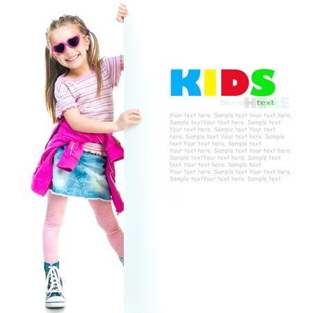 lustige kleine Mode-Mädchen hinter einem weißen Vorstand