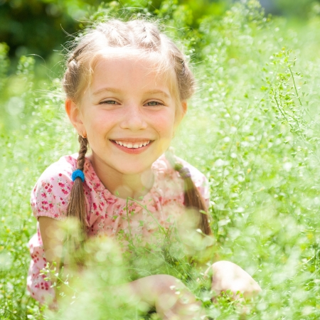 smiling little girl on the meadow in summer day