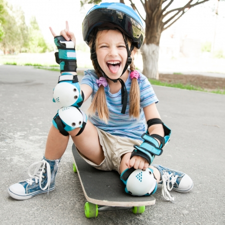 little cute girl with a helmet sitting on a skateboard photo