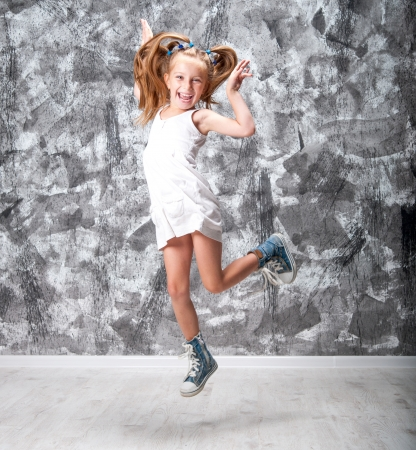 Cute little girl in dress jump  Studio shot  photo