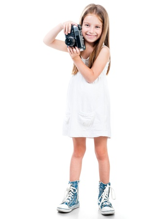photographing: little girl holding a camera on a white background Stock Photo