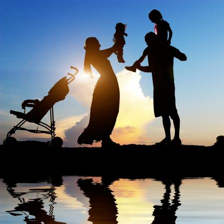 행복한 부모가 해안에 그들의 작은 아이들과 함께 좋은 시간을 보내고의 실루엣
