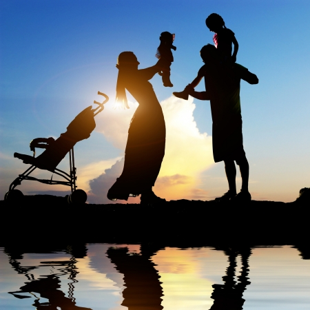 Silhouettes of happy parents having good time with their little children on the seacoast Foto de archivo