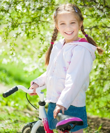 portrait of cute little girl on a bicycle photo