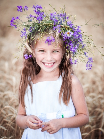 smiling little girl with a wreath on his head in a field of wheat