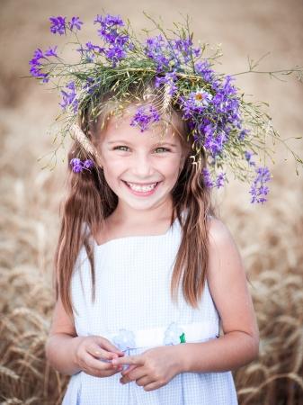 Niña sonriente con una corona de flores en la cabeza en un campo de trigo Foto de archivo - 20948154