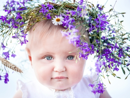 beautiful baby girl with a wreath on his head close-up photo