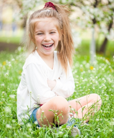 ptetty little girl on the meadow in solar summer day