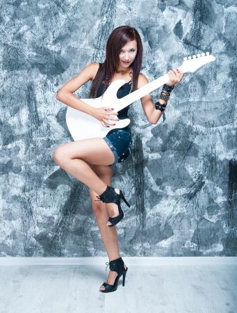 femme avec guitare: Beau chanteur de rock avec une guitare blanche en studio