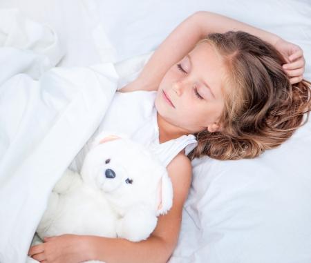 그녀의 테 디 베어와 함께 침대에서 잠을 아름다운 여섯 살 소녀 스톡 콘텐츠