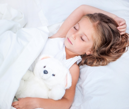 beautiful six year old girl sleeping in the bed with her teddy bear Foto de archivo