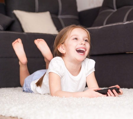 happy cute little girl holding a remote control photo