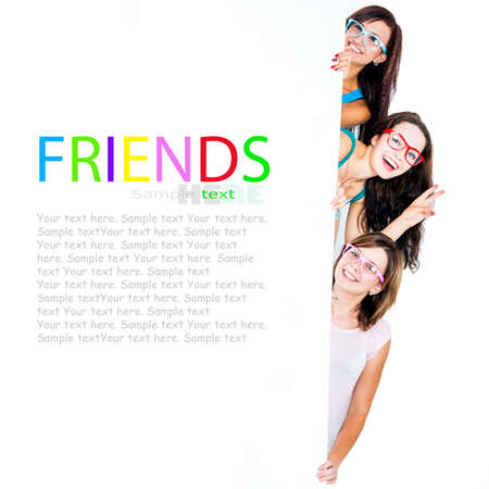 nice girls peeking from behind a blank banner with place for text photo