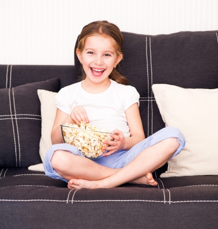 little girl eating popcorn in front of TV photo