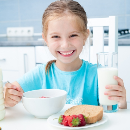 corn flakes: cute smiling little girl drinking milk in the kitchen Stock Photo