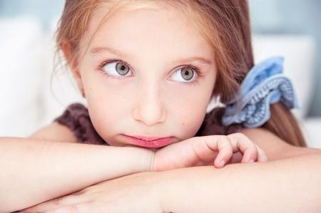sad child: sad little girl sitting at the table Stock Photo