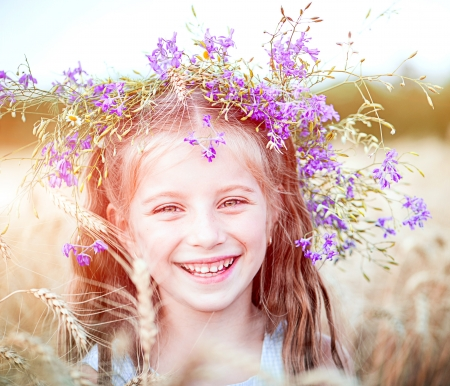 smiling little girl with a wreath on his head in a field of wheat close-up photo