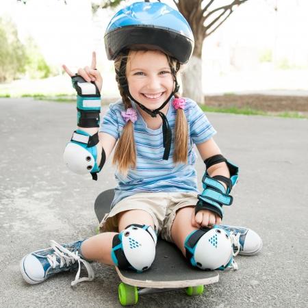 kleine hübsche Mädchen mit einem Helm sitzt auf einem Skateboard