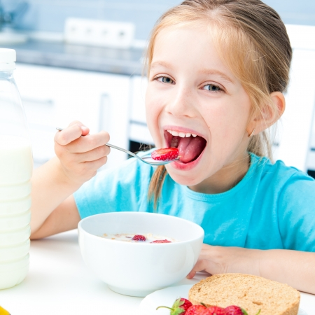 cute little girl eating cereal and strawberries in white kitchen