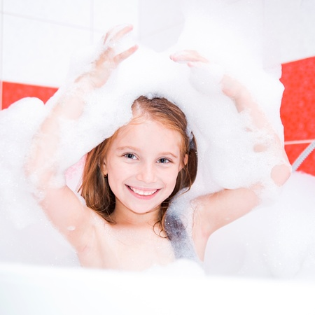 Small pretty girl is taking a bath with a foam photo
