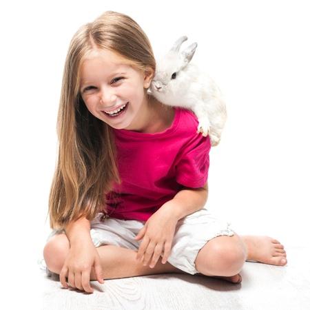glückliches kleines Mädchen in einem rosa T-Shirt mit einem kleinen weißen Kaninchen