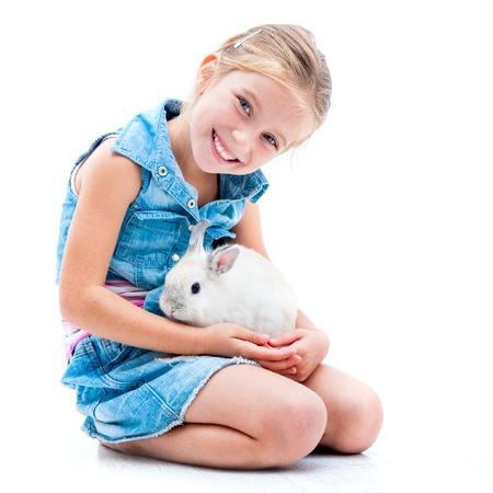 hübsche, kleine Mädchen in Denim Kleidung spielt mit weißen Kaninchen
