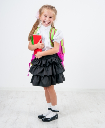 cute little girl with backpack studio isolated on white background photo