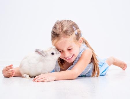 nettes lächelndes Mädchen in einem blauen Kleid mit einem weißen Kaninchen